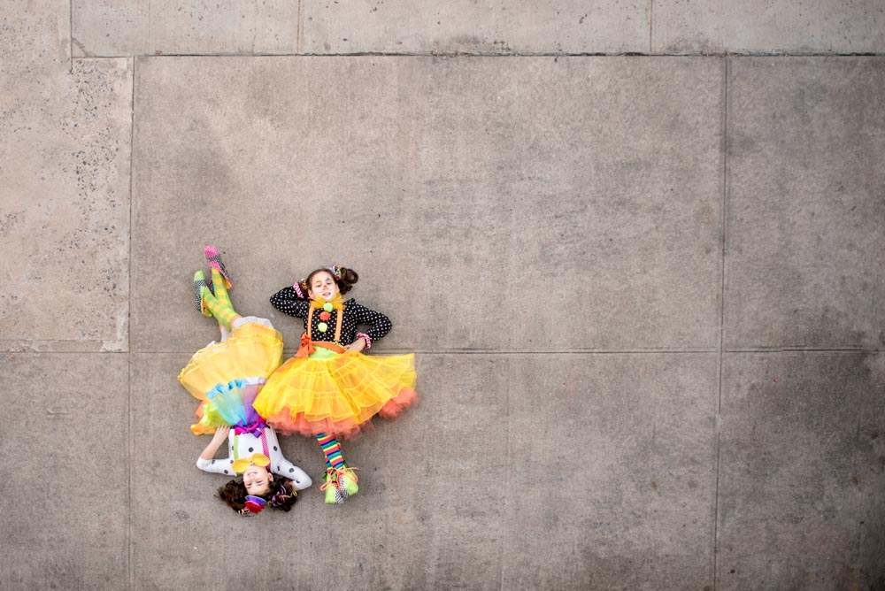 Purim clowns in colorful costume on asphalt in Brooklyn NY shot from above by Picadilly Studios