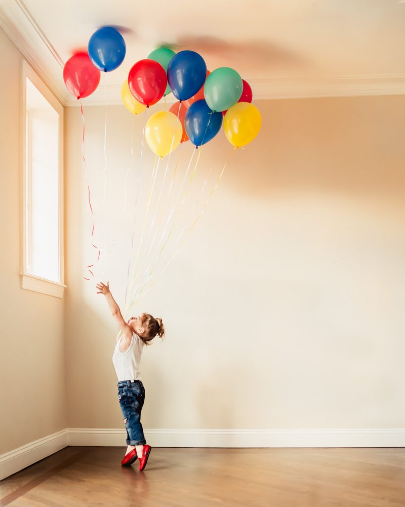 In-home photography session with little boy playing with colorful balloons, in Brooklyn NY.