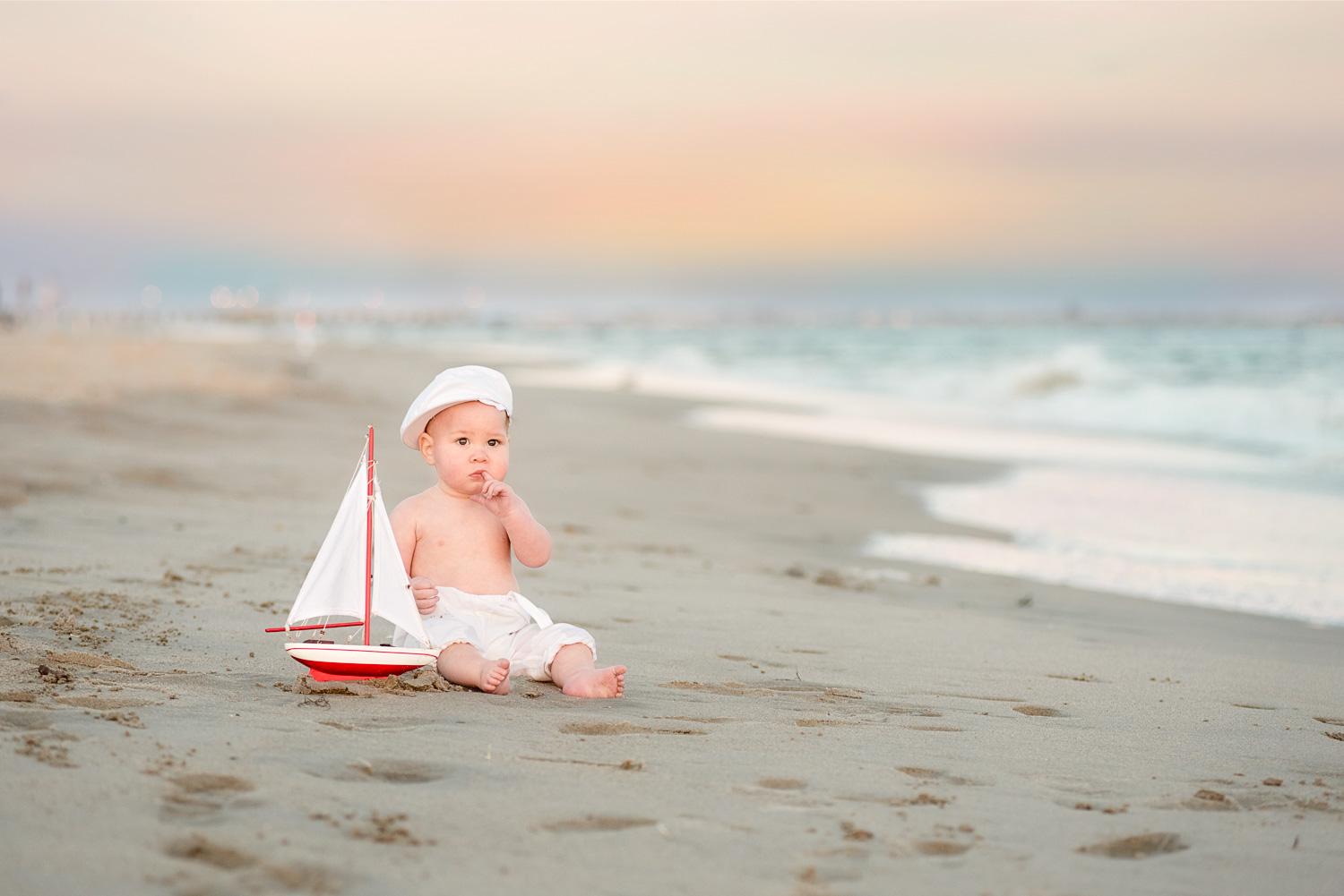 Portrait of baby in sand at sunset beach session at Coney Island Beach taken by Picadilly Studios
