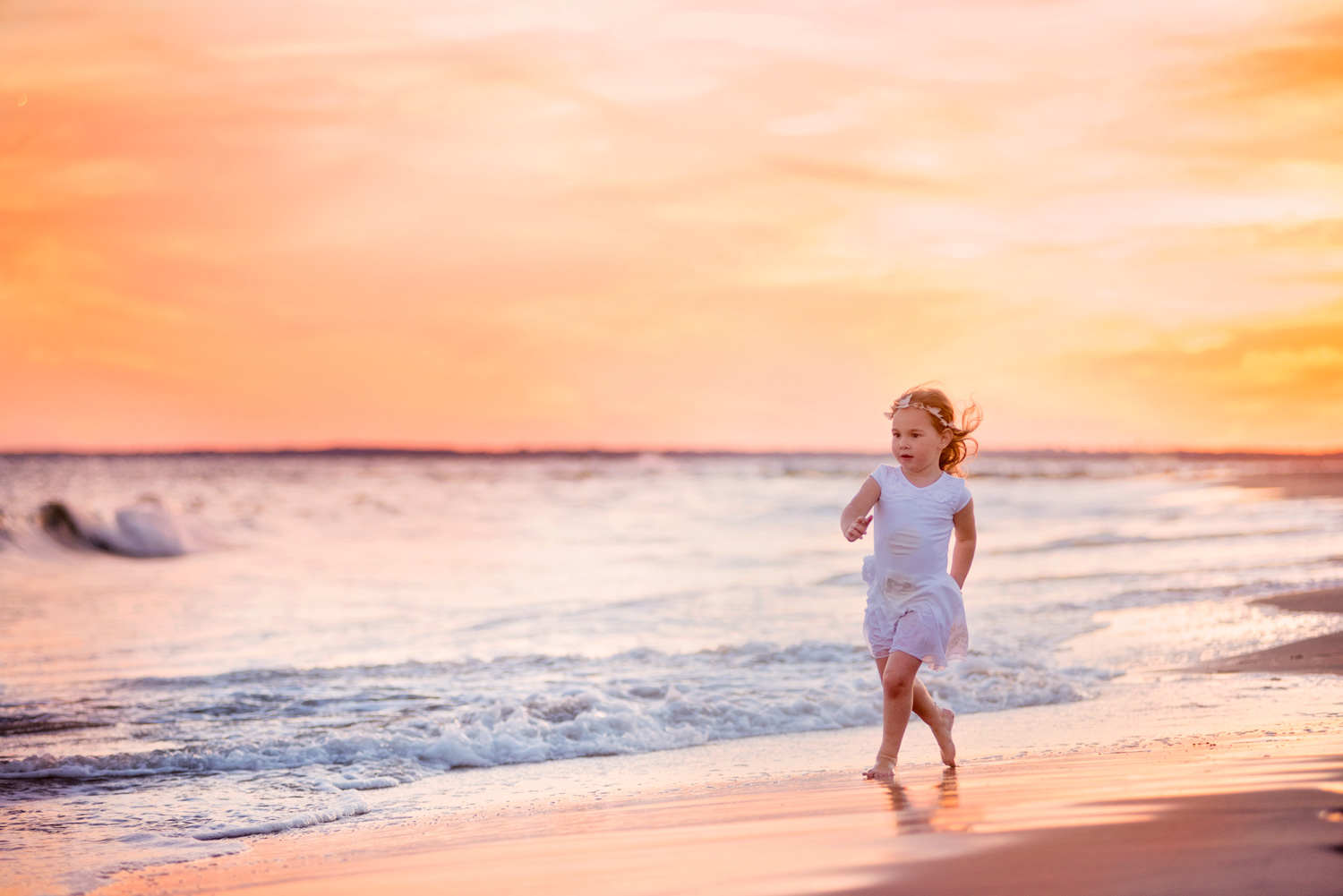 Girl running on the beach during sunset during a fun and relaxed photo session at Coney Island Beach