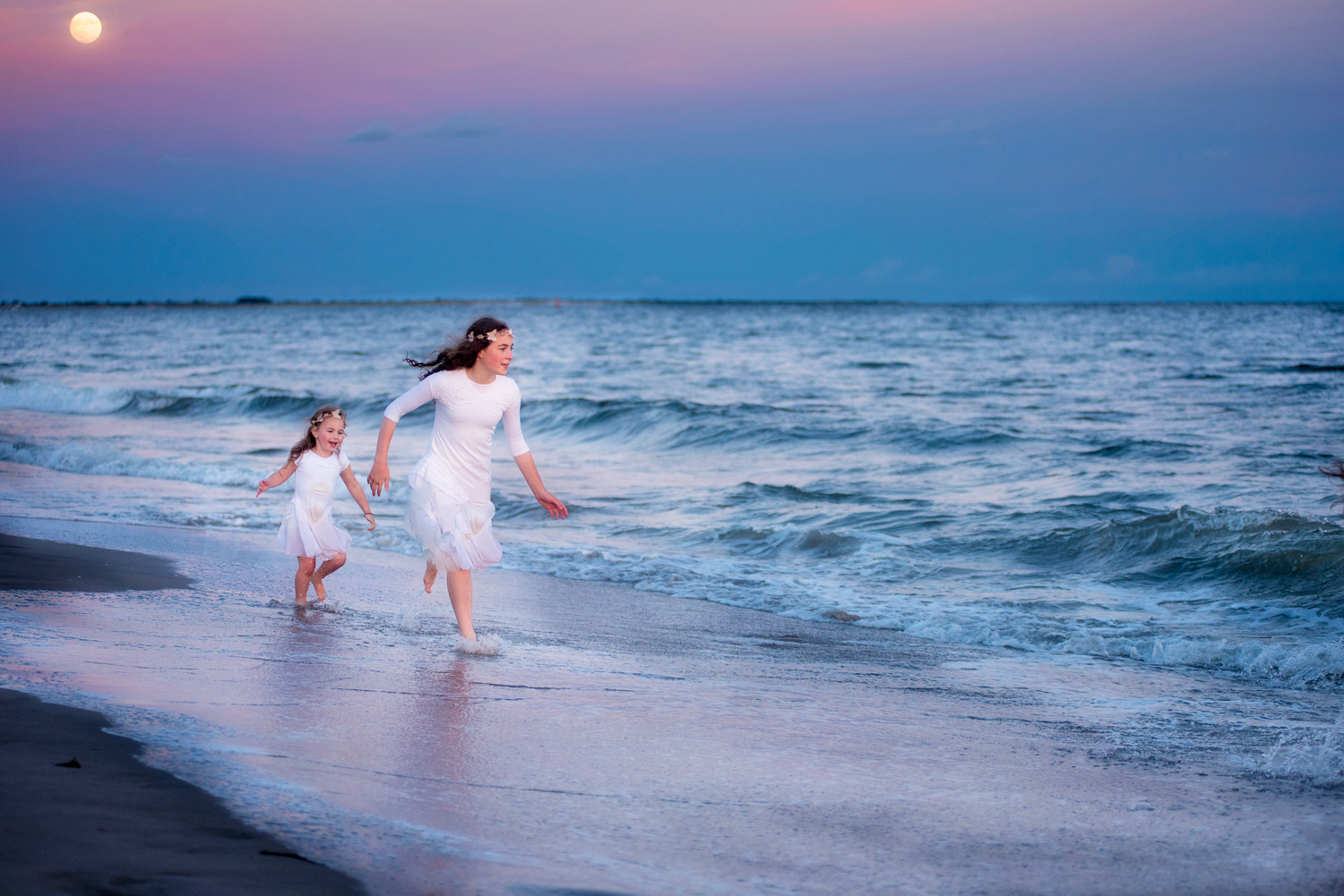 Fun and relaxed sunset photography session at Coney Island Beach in Brooklyn NY with sisters running in the waves taken by Picadilly Studios