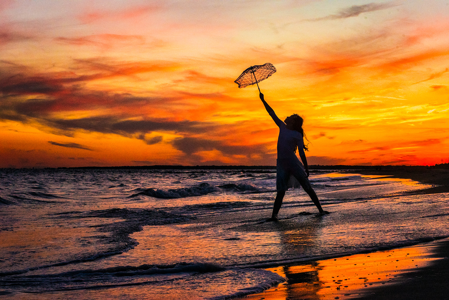 Silhouette of girl holding umbrella at Coney Island Beach by Picadilly Studios