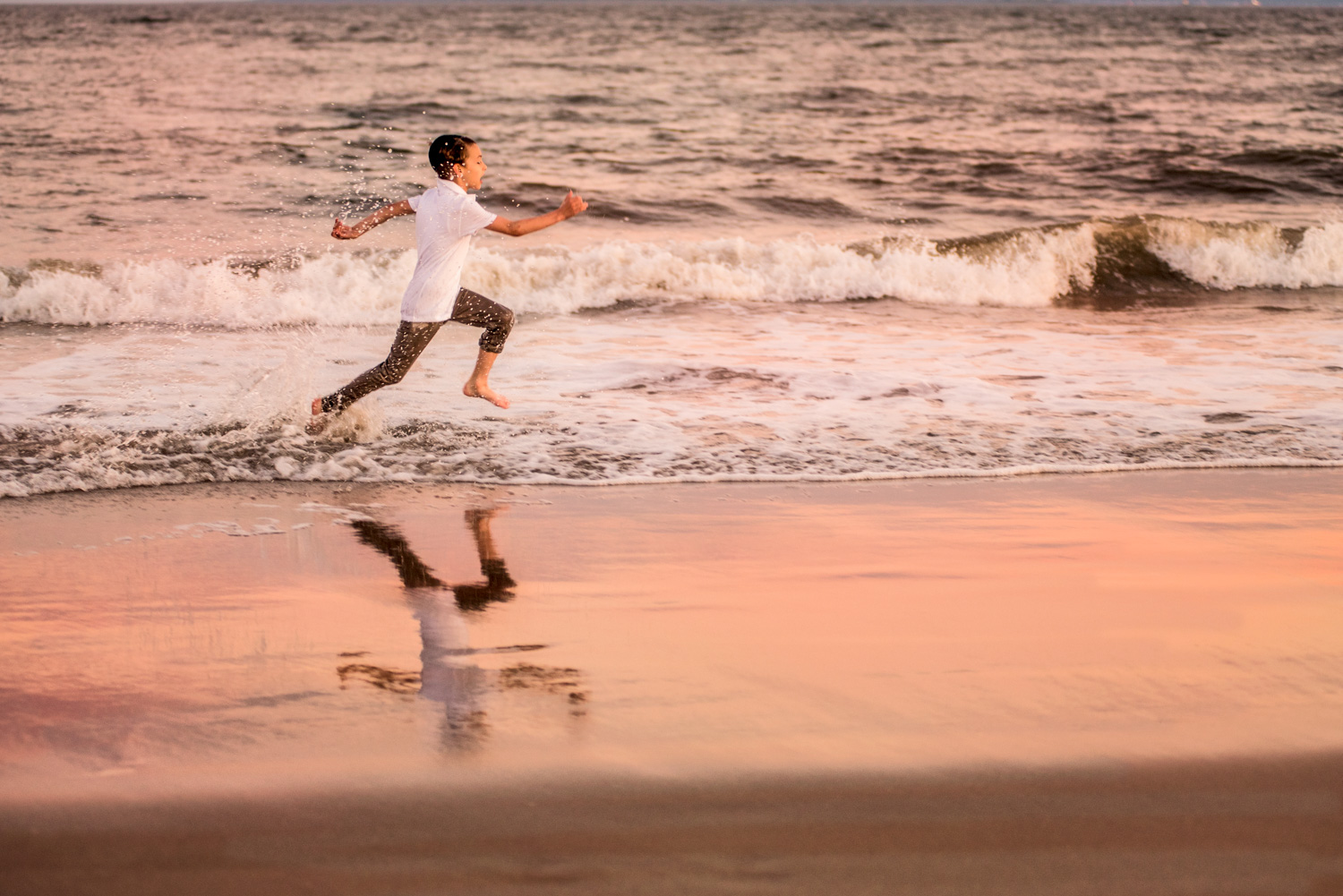 Portrait session at Coney Island Beach in Brooklyn NY of boy running in the wavesd