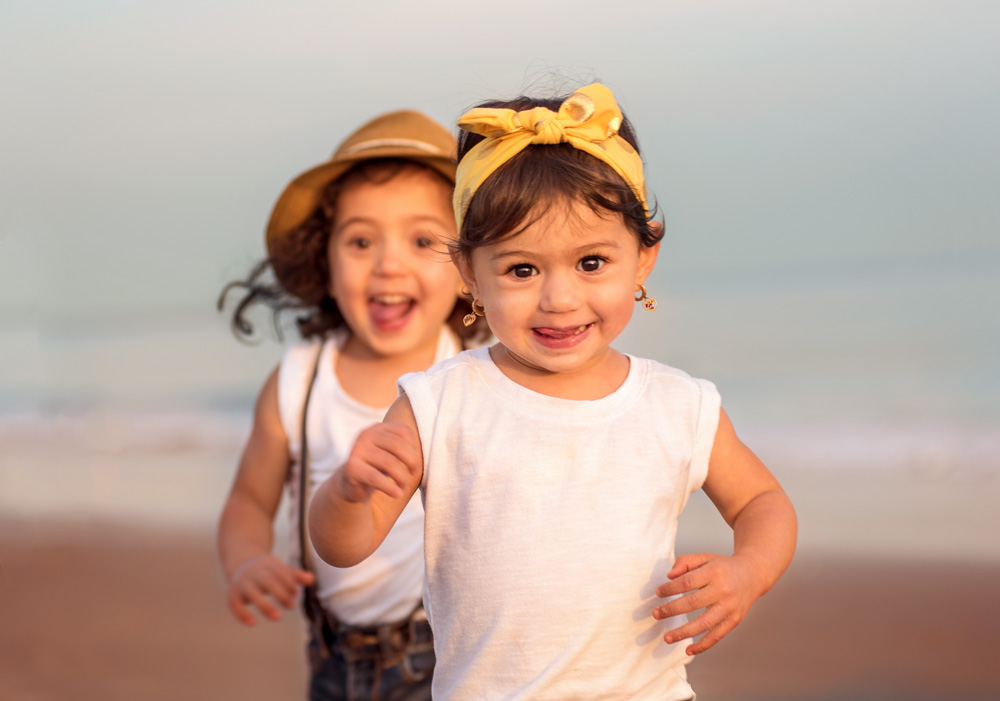 Photo session at Coney Island Beach in Brooklyn NY by Picadilly Studios of two young siblings having fun