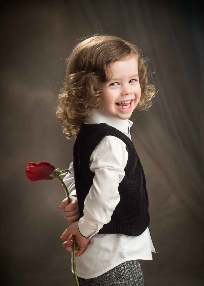 Upsherin photo session with adorable little boy holding a rose in Brooklyn NY by Picadilly Studios