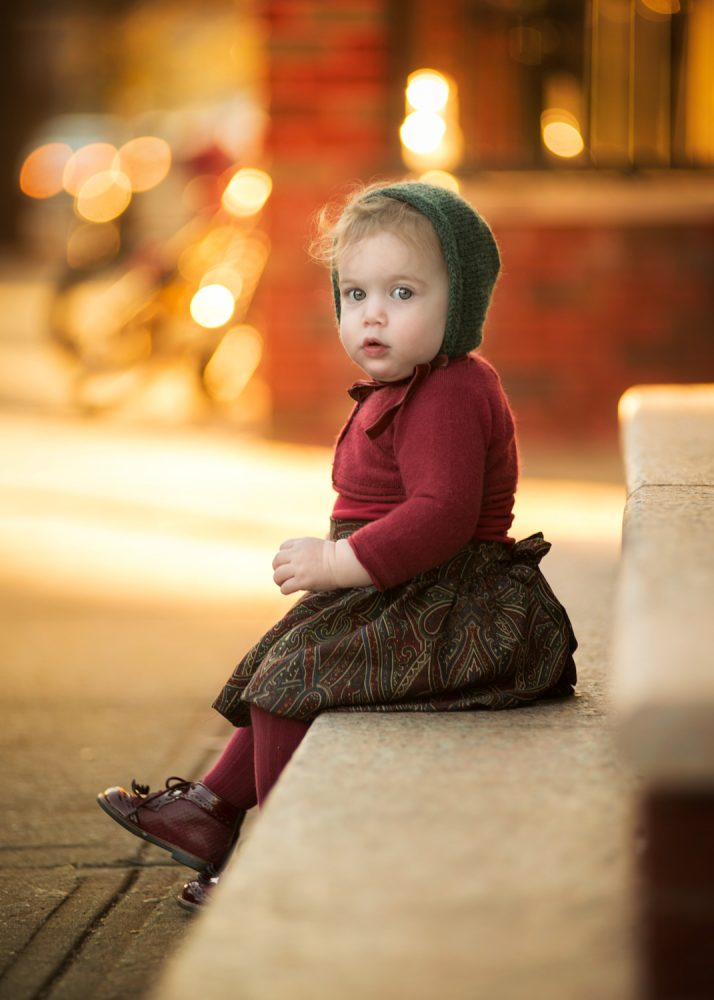 Portrait of baby girl sitting on steps during golden hour in Brooklyn NY wearing a handmade bonnet, taken by Picadilly Studios