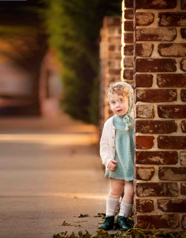 Portrait of little girl with curls in bonnet knit by mom standing by a brick pillar taken by Picadilly Studios in Brooklyn NY