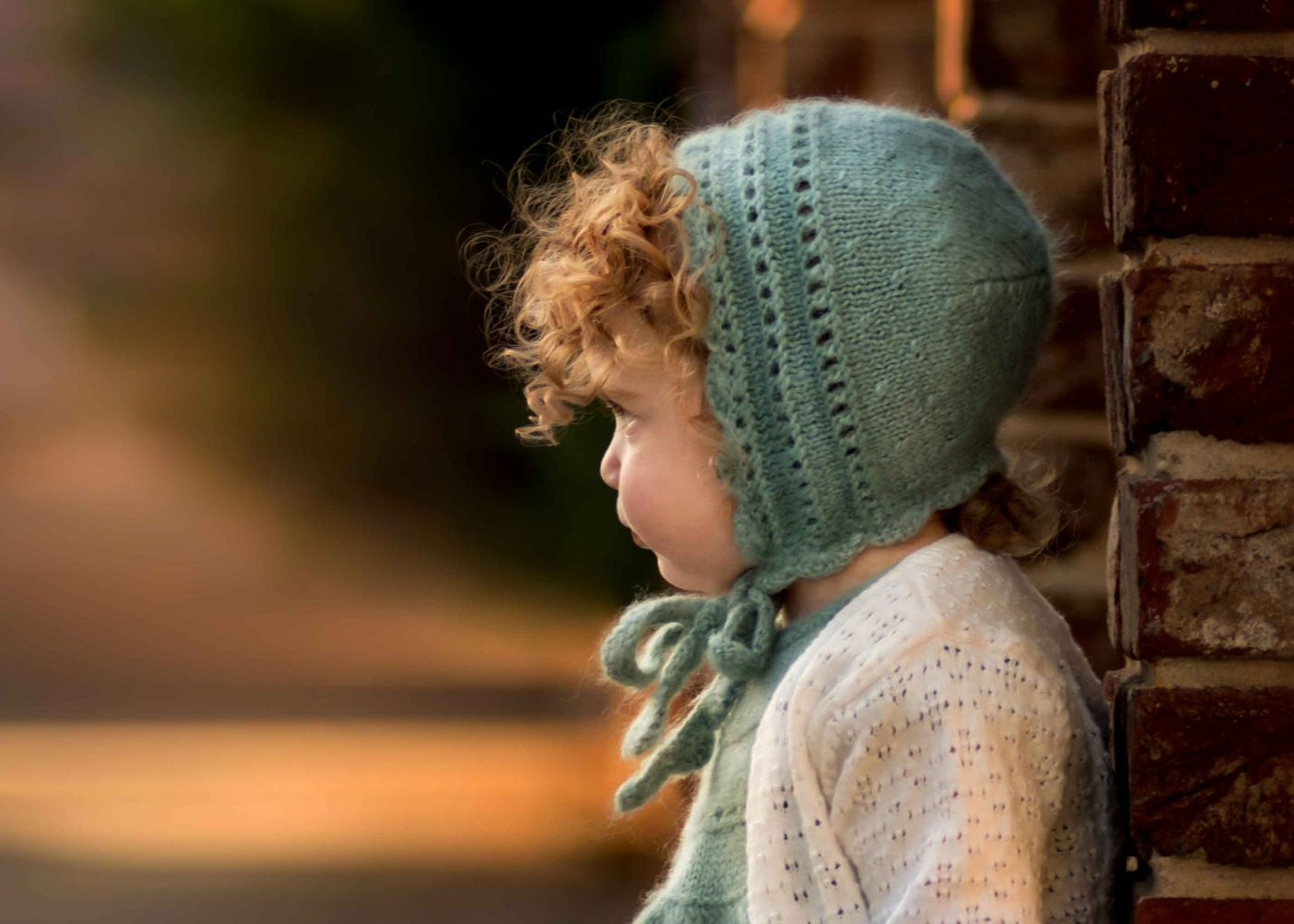 Brooklyn, NY portrait of little with handmade bonnet and curls standing by brick pillar