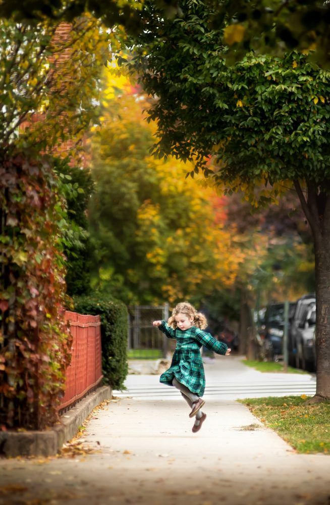 Little girl in Hanna Anderson dress in Brooklyn NY jumping with autumn colors