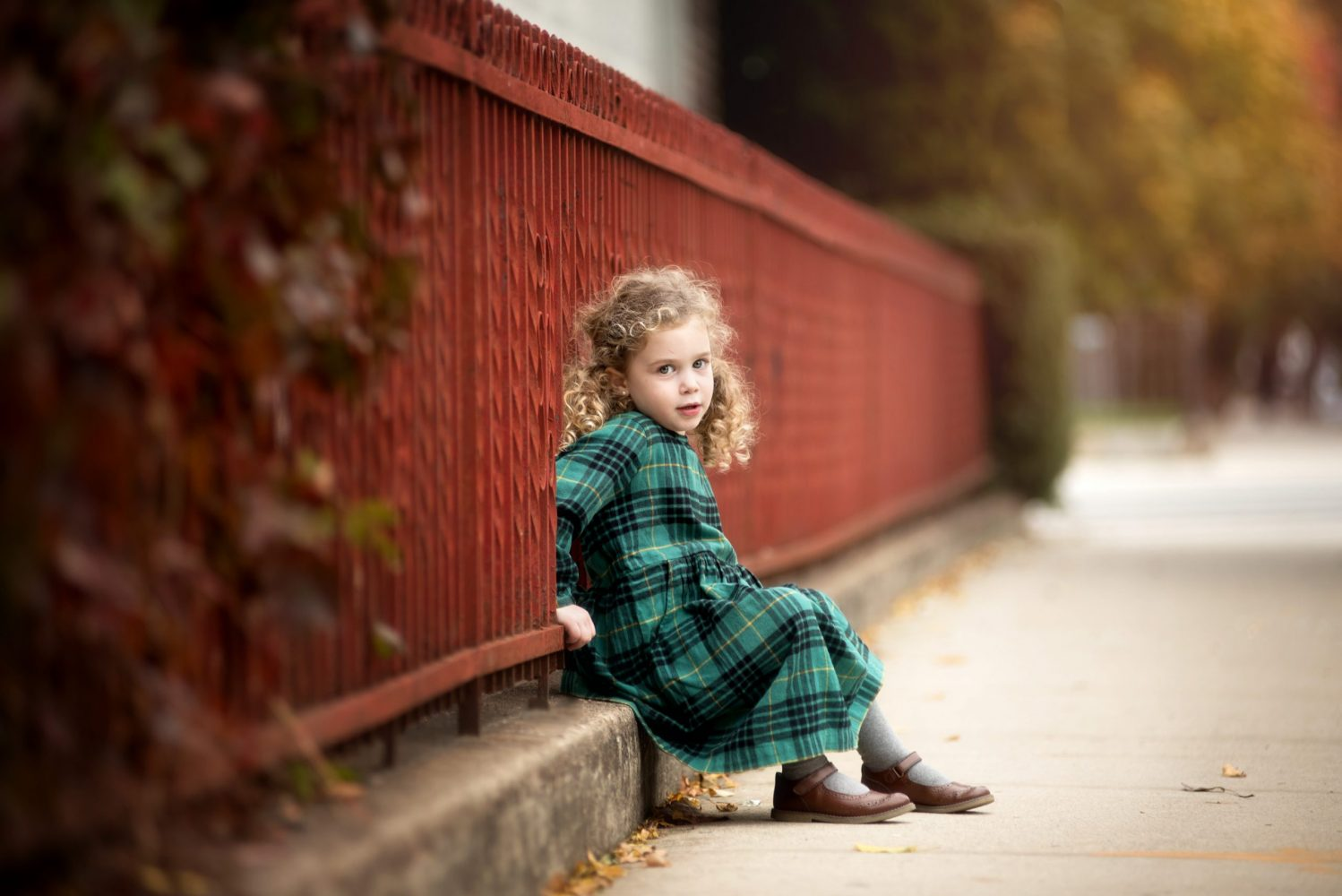 Portrait of little girl in plaid Hanna Anderson dress sitting by red gate in Brooklyn NY Hanna
