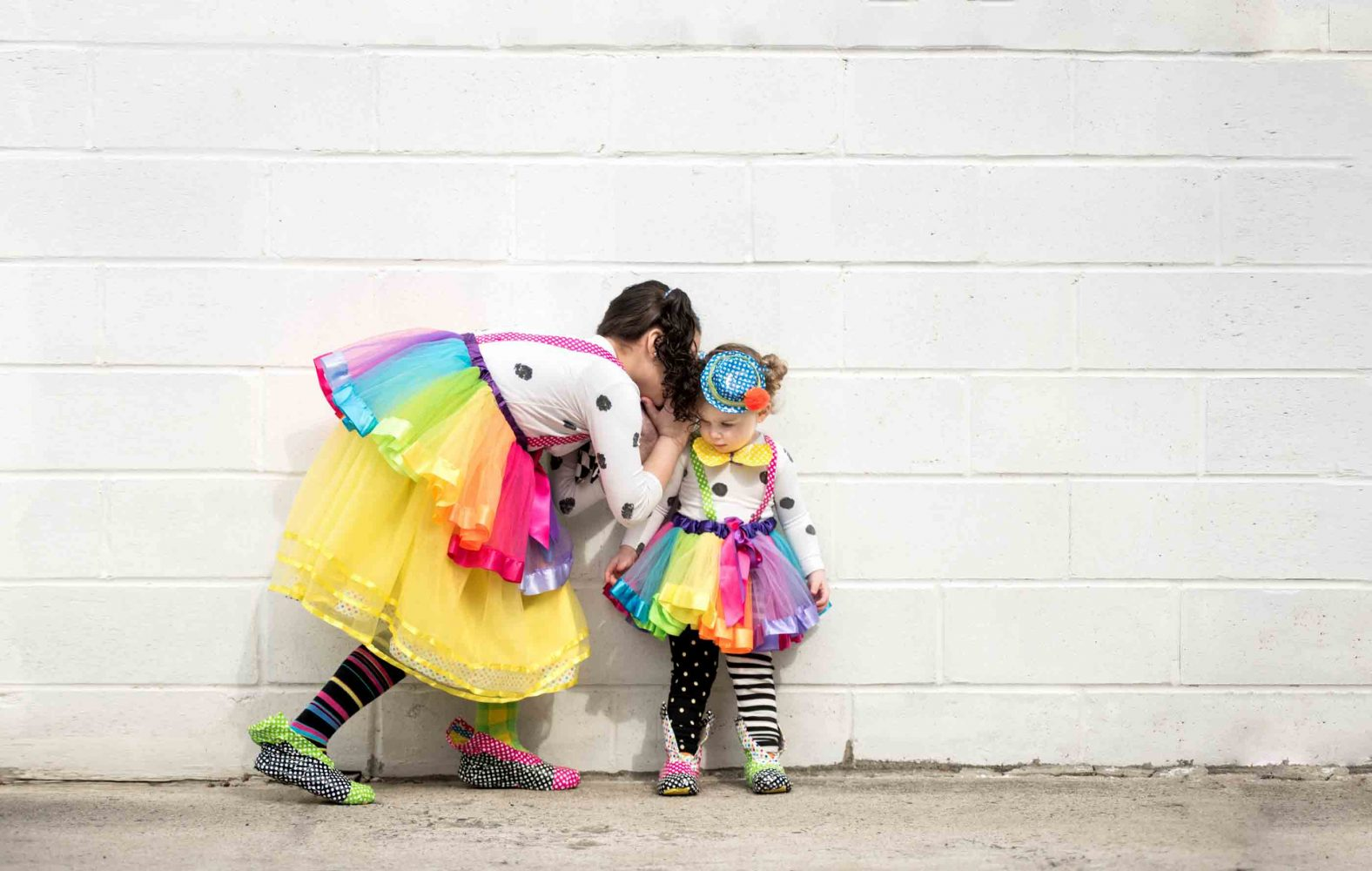 Purim portrait of two adorable clowns in costume by white wall in Brooklyn NY by Picadilly Studios