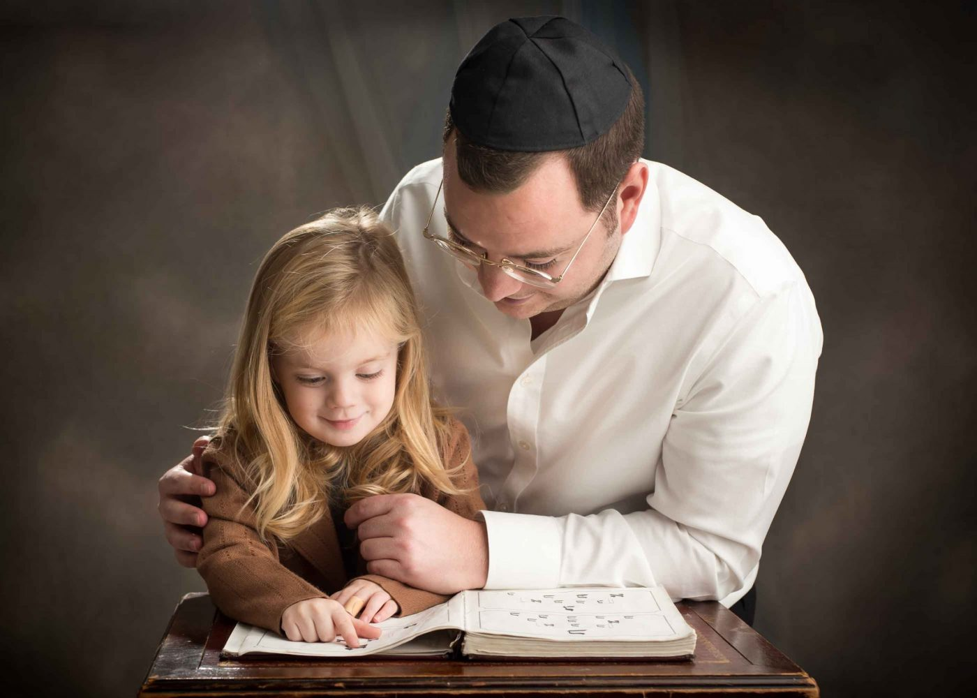 upsherin photo session in Brookly NY by Picadilly Studios of father and son learning the aleph bais together